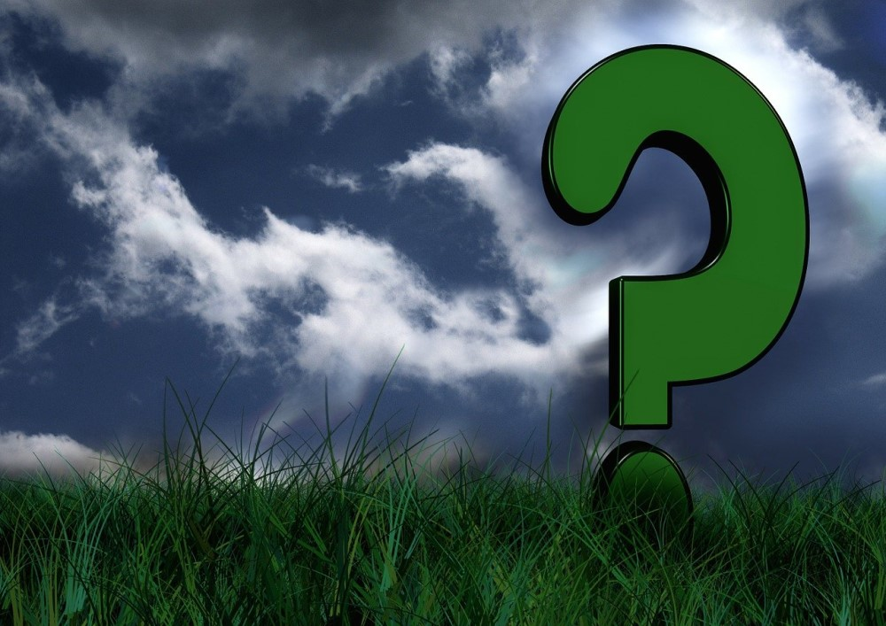 meadow and clouds in sky with question mark